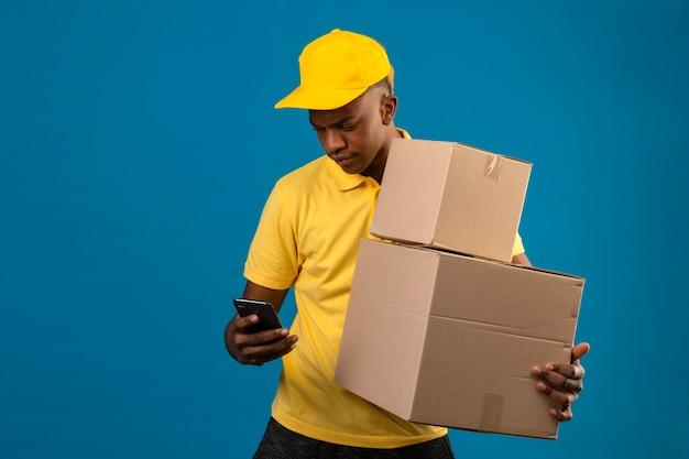 Livraison homme afro-américain en polo jaune et casquette tenant des boîtes en carton à l'écran de son téléphone mobile debout sur le bleu