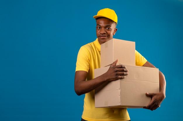 Livraison homme afro-américain en polo jaune et casquette tenant des boîtes en carton avec sourire amical debout sur bleu isolé