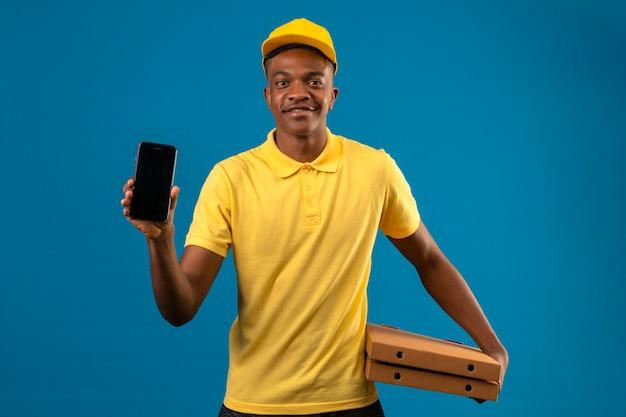 Livraison homme afro-américain en polo jaune et casquette tenant des boîtes de pizza montrant téléphone mobile avec sourire sur le visage debout sur bleu