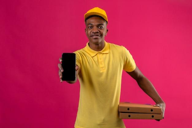 Livraison homme afro-américain en polo jaune et casquette tenant des boîtes à pizza montrant téléphone mobile avec sourire sur le visage debout sur rose