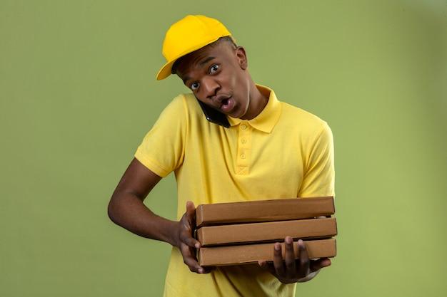 Livraison homme afro-américain en polo jaune et casquette tenant pile de boîtes à pizza tout en parlant au téléphone mobile à la surprise debout sur le vert