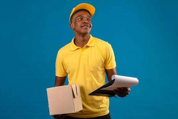 Livraison homme afro-américain en polo jaune et casquette tenant le presse-papiers et boîte en carton avec sourire confiant debout sur bleu isolé