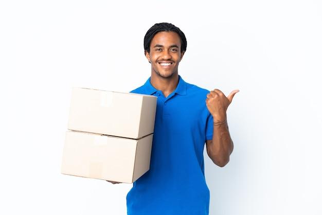 Livraison homme afro-américain avec des tresses isolé sur blanc pointant vers le côté pour présenter un produit
