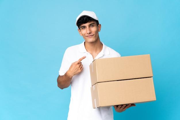 Livraison homme argentin isolé sur mur bleu pointant vers le côté pour présenter un produit