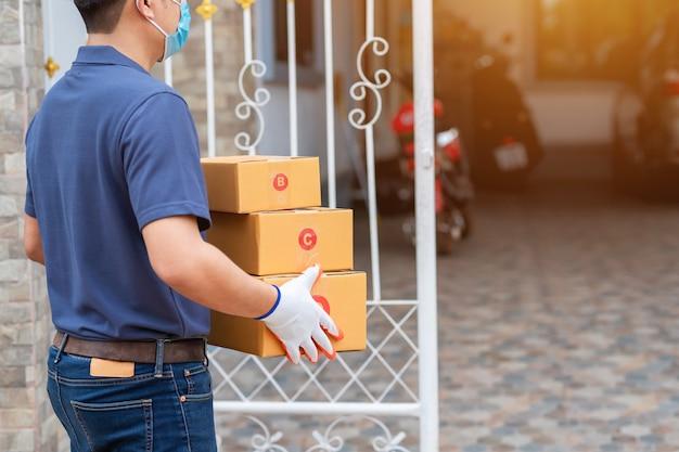 Livraison homme asiatique tenant des boîtes en carton dans des gants en caoutchouc médical et un masque. achats en ligne et livraison express ou commerce électronique. concept empêcher la propagation des germes et éviter les infections covid-19