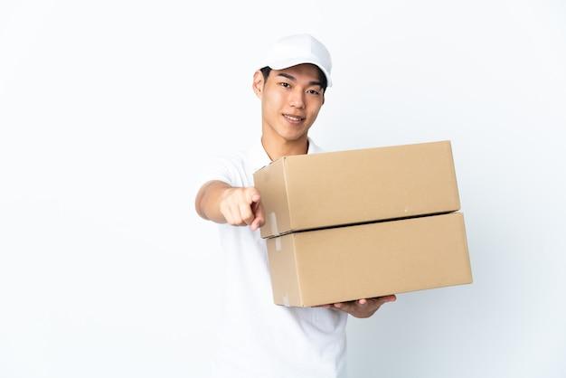 Livraison homme chinois isolé sur fond blanc pointant vers l'avant avec une expression heureuse