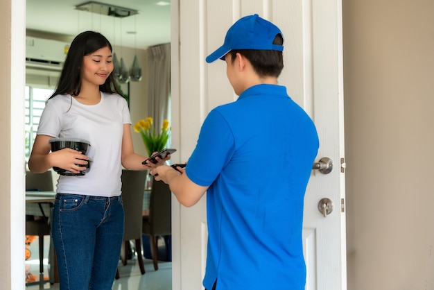 Livraison jeune homme en uniforme bleu sourire et tenant des boîtes de nourriture devant la maison