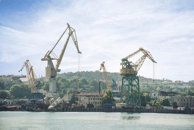 Une livraison mondiale, l'expédition de fret client, la grue industrielle lourde dans le port maritime