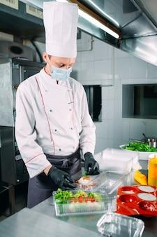 Livraison de nourriture au restaurant. le chef prépare la nourriture au restaurant et l'emballe dans des plats jetables.