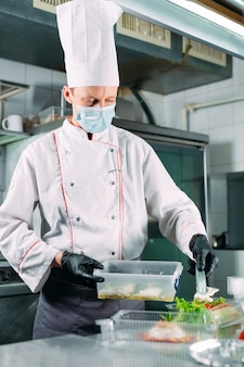Livraison de nourriture au restaurant. le chef prépare les plats au restaurant et les emballe dans des plats jetables.