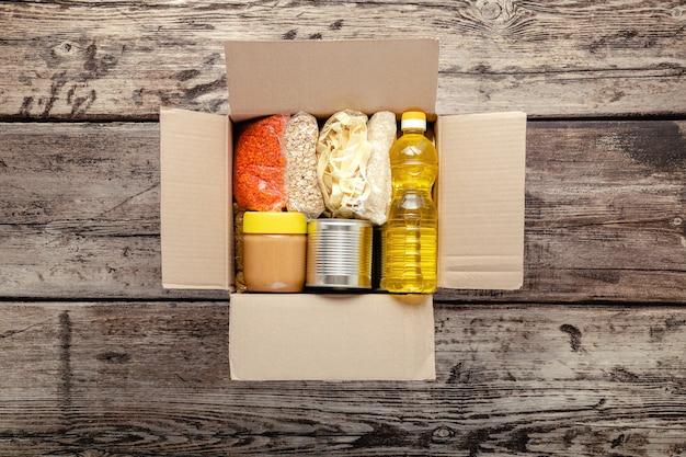 Livraison de nourriture ou boîte de dons pendant la quarantaine covid. livraison à domicile sociale sans contact, achats en toute sécurité en cas de pandémie de coronavirus. repas à emporter. boîte de nourriture sur le seuil près de la porte. livraison par coursier à domicile.