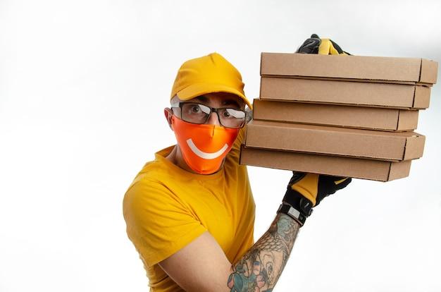 Livraison de nourriture et de marchandises en quarantaine, le gars livrant des colis dans un masque anti-virus, le coursier avec pizza