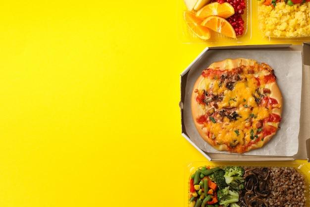 Livraison de nourriture. nourriture dans des boîtes à emporter sur mur jaune