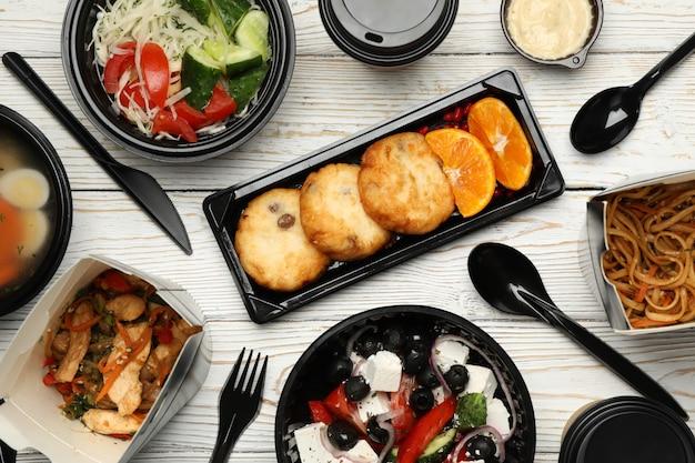 Livraison de nourriture. nourriture dans des boîtes à emporter sur table en bois