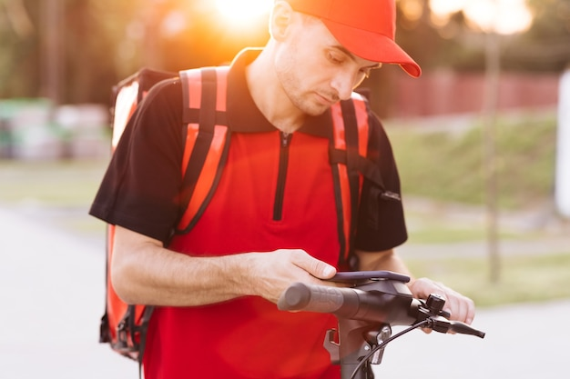 La livraison de nourriture par courrier d'homme avec le sac à dos thermique rouge marche la rue avec le scooter électrique