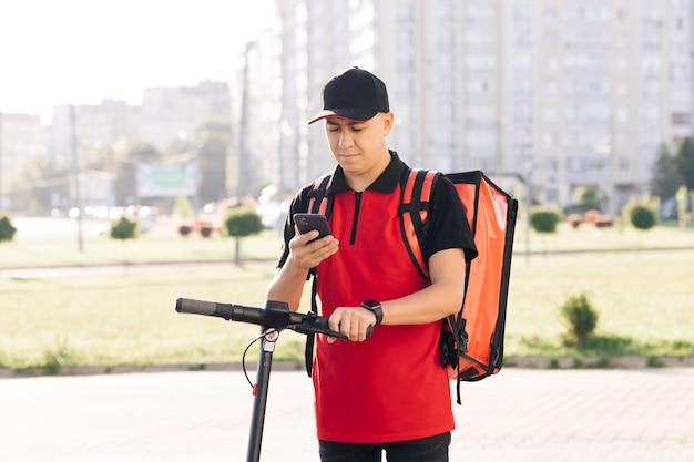 Livraison de nourriture par coursier masculin avec sac à dos thermique rouge regarde autour de la rue avec des utilisations de scooter électrique