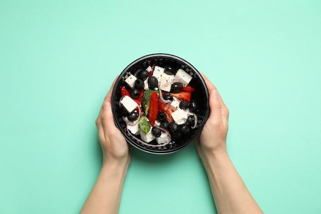 Livraison de nourriture. personne détient une salade dans une boîte à emporter sur le mur de menthe
