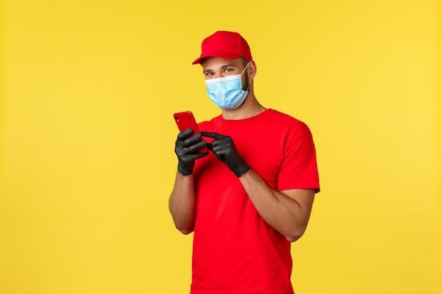 Livraison de nourriture, suivi des commandes, covid-19 et concept d'auto-quarantaine. souriant gentil courrier en uniforme rouge, masque médical et gants, utilisant un téléphone portable et un appareil photo, fond jaune