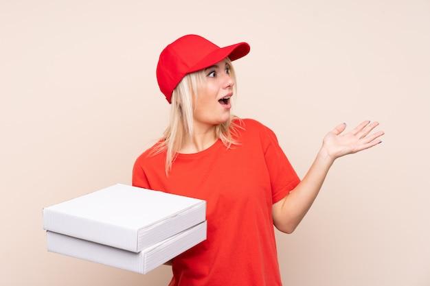 Livraison de pizza femme russe tenant une pizza sur un mur isolé avec une expression faciale surprise