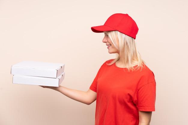 Livraison de pizza femme russe tenant une pizza sur un mur isolé avec une expression heureuse