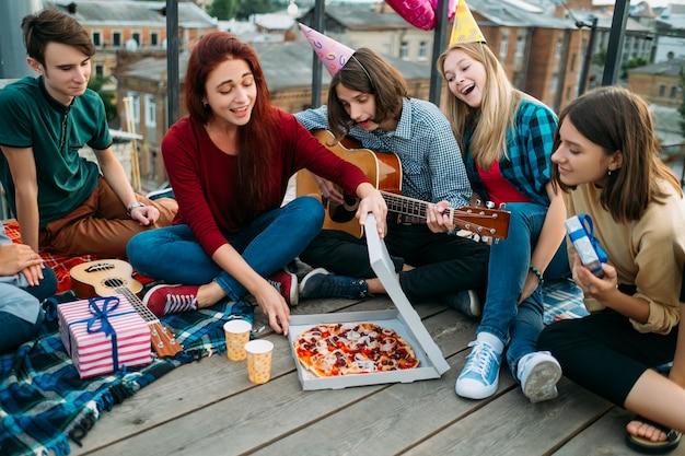 Livraison de pizza sur le toit. nourriture d'anniversaire non conventionnelle. préférences alimentaires des jeunes. nourriture savoureuse et délicieuse. adolescents affamés heureux