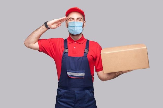Livraison en quarantaine. saluez ou oui monsieur ! jeune homme avec masque médical chirurgical en uniforme bleu et t-shirt rouge debout, tenant une boîte en carton sur fond gris. intérieur, tourné en studio, isolé.
