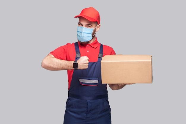 Livraison en quarantaine. service à l'heure ! homme avec masque médical chirurgical en uniforme bleu et t-shirt rouge debout, tenant une boîte de livraison et montrant une montre sur fond gris. prise de vue en intérieur, isolée,