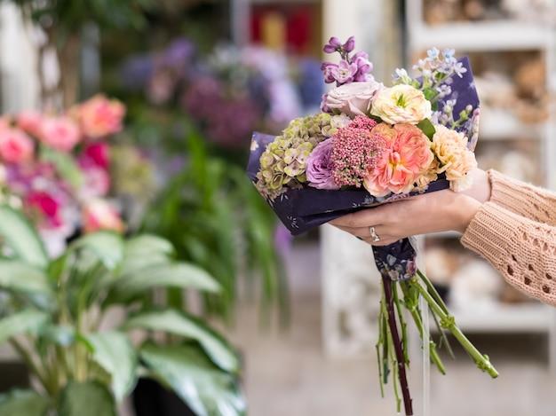 Livraison rapide de bouquets de fleurs pour un jour spécial - anniversaire ou anniversaire. mains de femmes tenant un arrangement créatif de roses pivoines hortensias et lilas