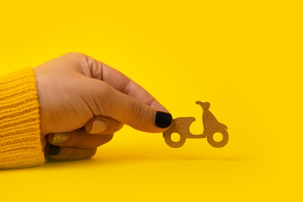 Livraison rapide et gratuite en scooter, scooter en bois en main sur fond jaune