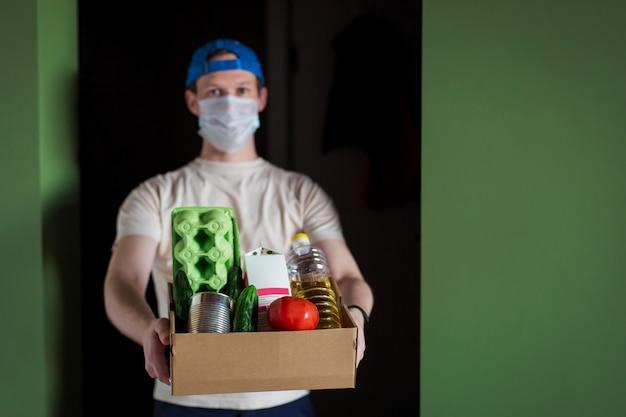 Livraison rapide sans contact. jeune homme masqué livre une boîte de nourriture saine.