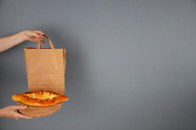 Livraison de repas géorgiens, main tenant un paquet de papier et bateau de fromage avec du jaune d'oeuf sur une planche à découper en bois à la main sur fond gris