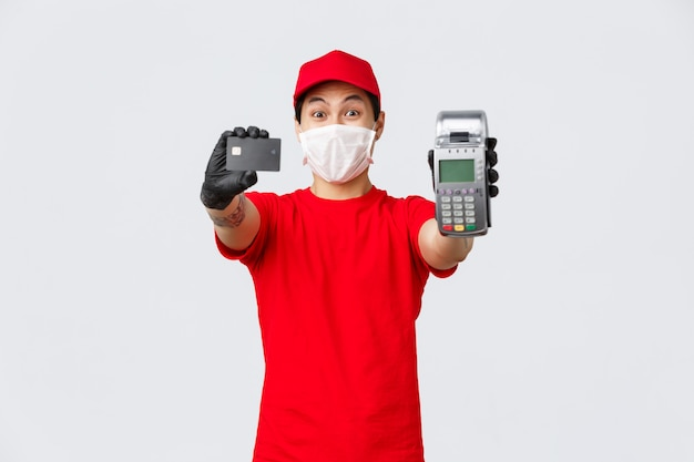 Livraison sans contact, achat en toute sécurité et achats pendant le concept de coronavirus. courrier asiatique excité en uniforme rouge, masque médical et gants de protection recommandent d'utiliser une carte de crédit et un terminal de point de vente