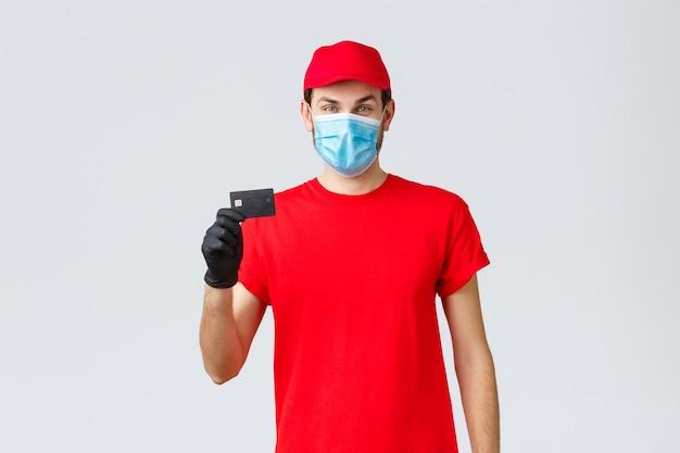 Livraison sans contact, paiement et achats en ligne pendant covid-19, auto-quarantaine. jeune coursier en bonnet d'uniforme rouge, masque facial et gants, montrant une carte de crédit, un paiement et une commande faciles