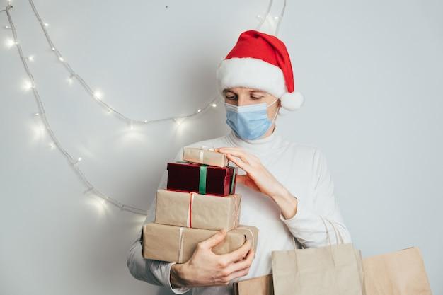 Livraison sécurisée de noël et du nouvel an, messager en bonnet rouge et masque de protection pendant la quarantaine du coronavirus. cadeaux et maison