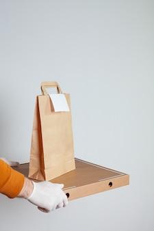 Livraison Sûre De Nourriture Dans Un Sac Artisanal Et Livreur De Pizza à La Maison Sur Un Fond Blanc Photo Premium