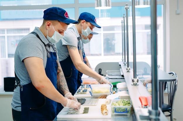 Livraison de sushi. des chefs masqués et gantés préparent des sushis dans la cuisine du restaurant.