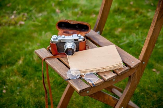 Livre et appareil photo vintage sur une chaise sur l'herbe verte
