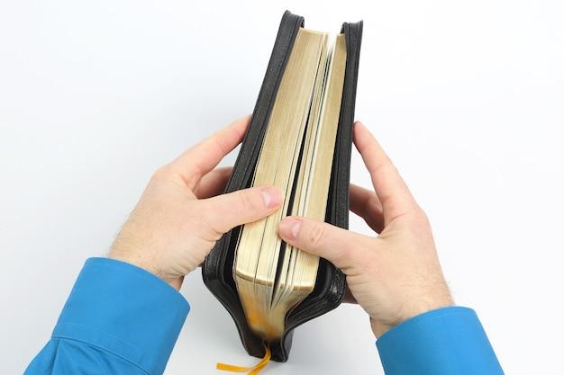 Livre de la bible dans les mains sur fond blanc. éducation et spiritualité