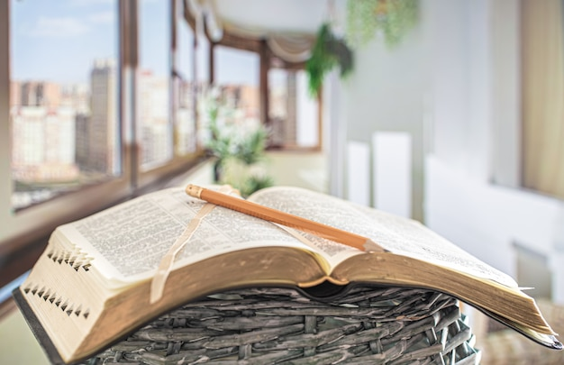 Livre bible avec gros plan au crayon, sur une belle terrasse.