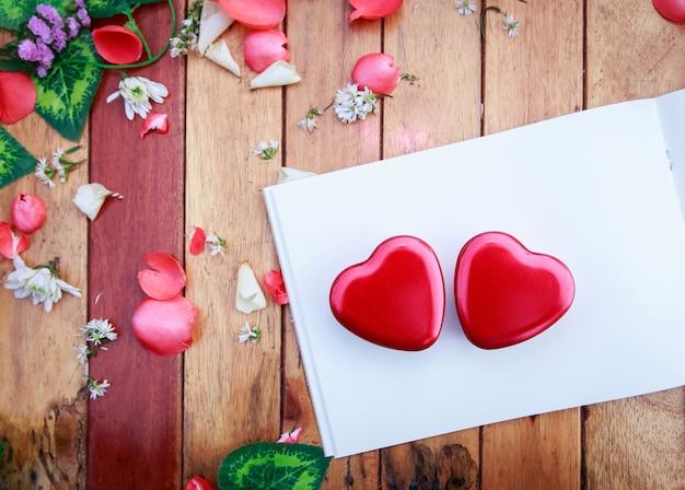 Livre blanc et boîte de coeur rouge avec pétales de fleurs décoratives sur table en bois. fond pour vale