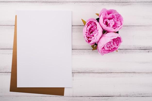 Livre blanc sur le bureau en bois avec fleur et ciseaux