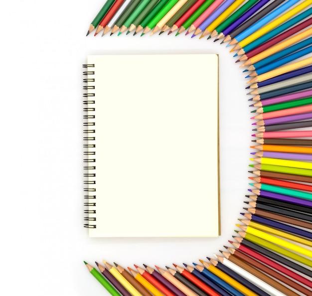 Livre blanc entouré de crayons de différentes couleurs