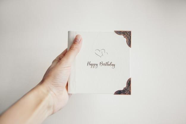 Un livre blanc enveloppé de cuir sur fond blanc. album photo avec un cadre en métal. carte de voeux