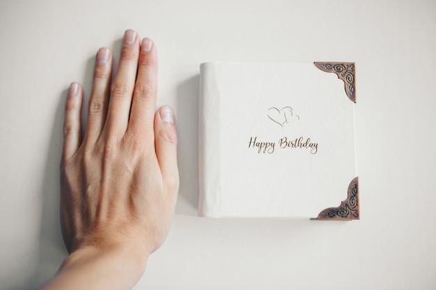 Un livre blanc enveloppé de cuir sur un fond blanc
