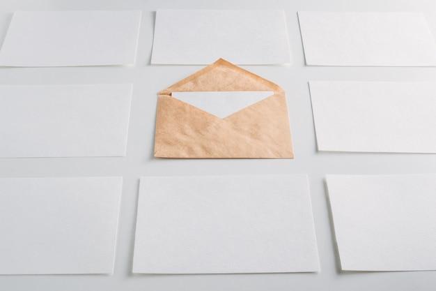 Livre blanc feuilles vides cartes et enveloppe kraft sur fond blanc.