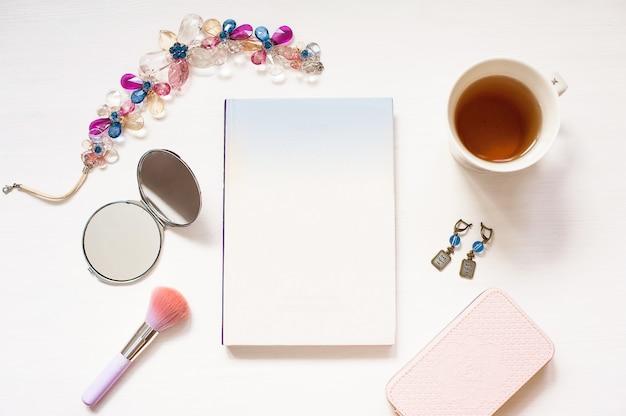 Livre blanc isolé sur fond de bois texturé blanc avec accessoires femmes mignonnes