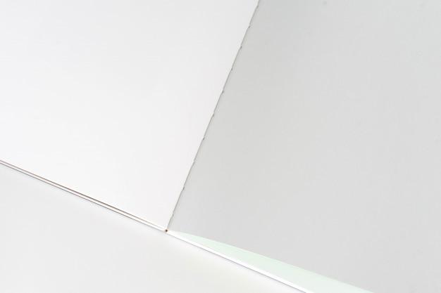 Livre blanc ouvert au fond de papier de conception gris blanc.