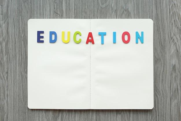 Livre blanc ouvert avec lettres education sur table en bois.