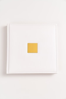 Livre blanc en reliure cuir avec insert en métal doré pour inscription. produits d'impression. livres et albums photos. produits individuels.