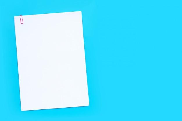 Livre blanc avec un trombone sur fond bleu.